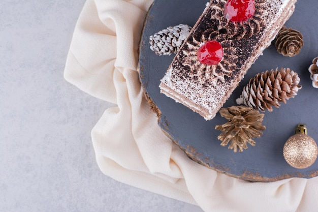 Stück kuchen mit weihnachtsschmuck auf holzstück.
