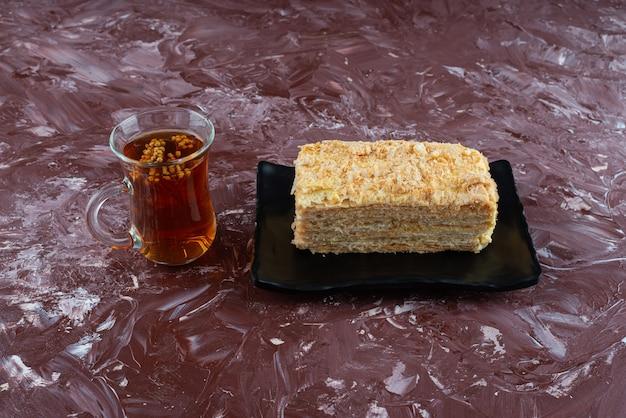 Stück kuchen napoleon auf schwarzem tablett mit einem glas kräutertee.