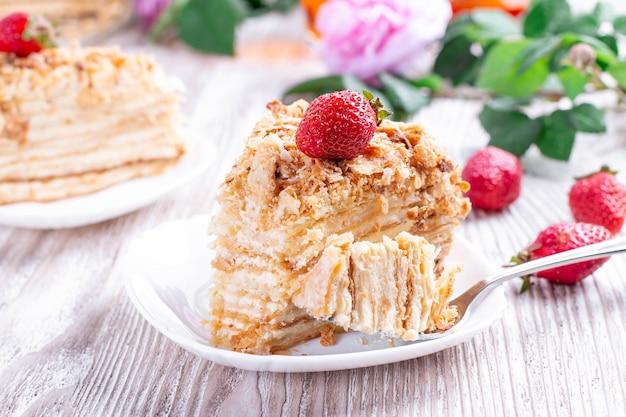 Stück kuchen napoleon auf weißem teller. russische küche, schichtkuchen mit gebäckcreme, nahaufnahme