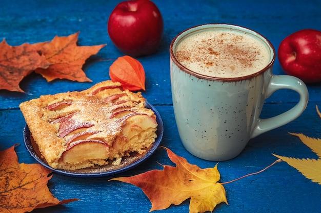 Stück kuchen, tasse kaffee mit milch, trockenes herbstlaub, rote äpfel auf einem blauen holztisch
