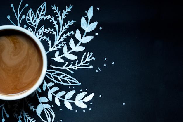 Stück kuchen und eine tasse kaffee auf schwarzem hintergrund mit neujahr dekoriert. gemalte weiße schneeflocke.