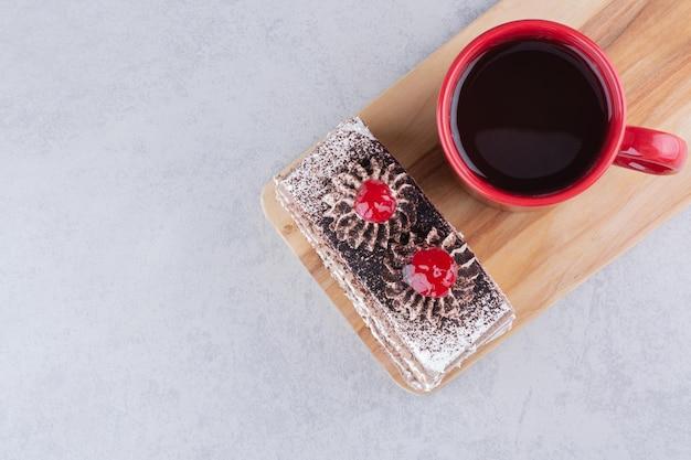 Stück kuchen und eine tasse tee auf holzbrett. foto in hoher qualität