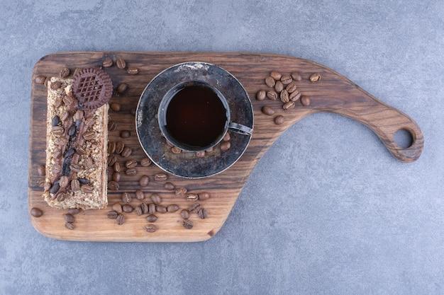 Stück kuchen und kaffeebohnen neben einer tasse kaffee auf einem brett auf marmoroberfläche