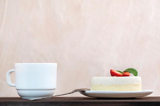 Stück kuchen und tasse kaffee, seitenansicht. mit erdbeeren garniertes stück käsekuchen.