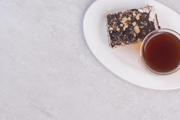 Stück kuchen und tasse tee auf weißem teller.