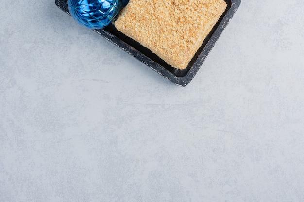 Stück kuchen und weihnachtskugeln auf einem kleinen schwarzen tablett auf marmoroberfläche