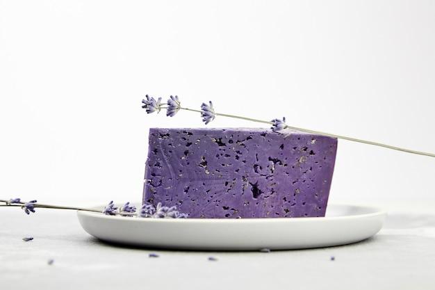 Stück lavendelkäse mit trockenem basilikum und blumen in platte auf betontisch
