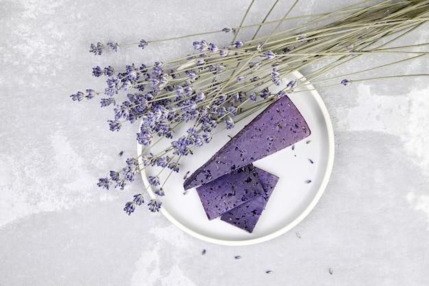 Stück lavendelkäse mit trockenem basilikum und lavendelblüten im teller auf grauer tischoberansicht