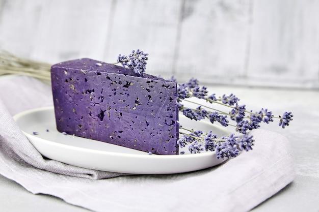 Stück lavendelkäse mit trockenem basilikum und lavendelblüten in teller auf betontisch