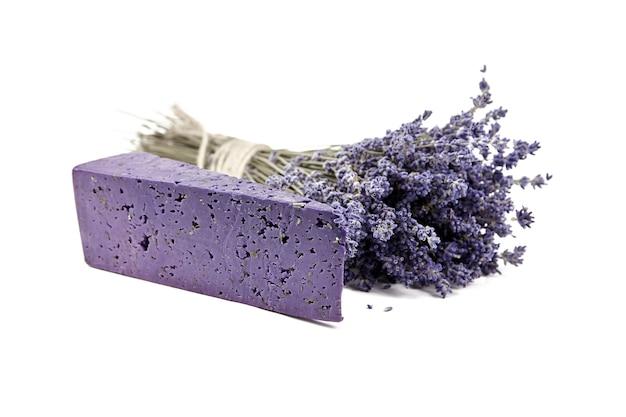 Stück lavendelkäse mit trockenem basilikum und lavendelblüten isoliert