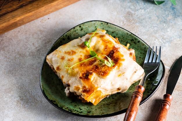 Stück leckere heiße lasagne mit rotwein. kleine schärfentiefe. traditionelle italienische lasagne. portion. italienisches essen. essen auf grünem teller. bolognese-sauce. bechamelsauce. stillleben des essens.