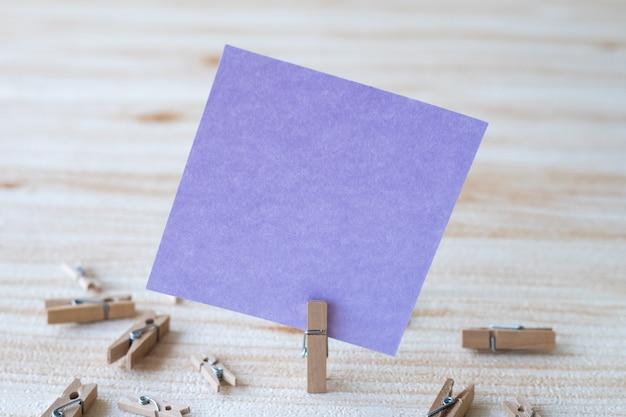 Stück leere quadratische notiz, umgeben von wäscheklammern, die eine neue bedeutung zeigen, leeres klebriges papier
