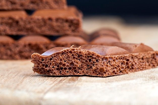 Stück luftschokolade mit kakao und zucker, in stücke geteilt tafelschokolade, luftmilchschokolade in stücke gebrochen