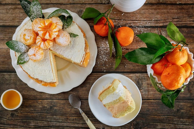 Stück mandarinen-biskuit mit ganzen frischen mandarinen dekoriert