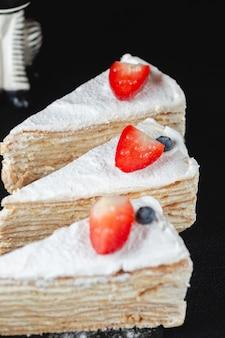 Stück marshmallow-kuchen mit erdbeeren auf dunklem hintergrund