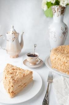 Stück mehrschichtiger napoleon-kuchen mit buttercreme auf einem weißen teller nahaufnahme neben einem teller ist eine serviette und eine gabel im hintergrund eine tasse teekanne und eine vase mit blumen weißer hintergrund