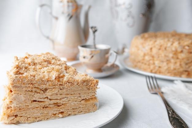 Stück mehrschichtiger napoleon-kuchen mit buttercreme auf einem weißen teller nahaufnahme neben einem teller ist eine serviette und eine gabel im hintergrund ist eine tasse teekanne und eine vase mit blumen unscharfer hintergrund
