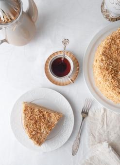 Stück mehrschichtiger napoleon-kuchen mit buttercreme. auf einem weißen teller. von oben betrachten. neben einem teller stehen eine serviette, eine gabel, eine tasse tee, eine teevase mit blumen. weißer hintergrund.