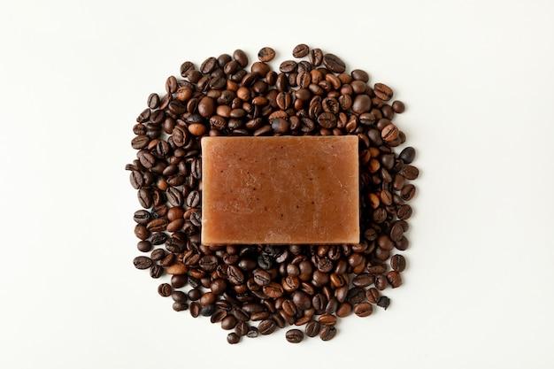 Stück natürliche seife und kaffeesamen auf weißer oberfläche
