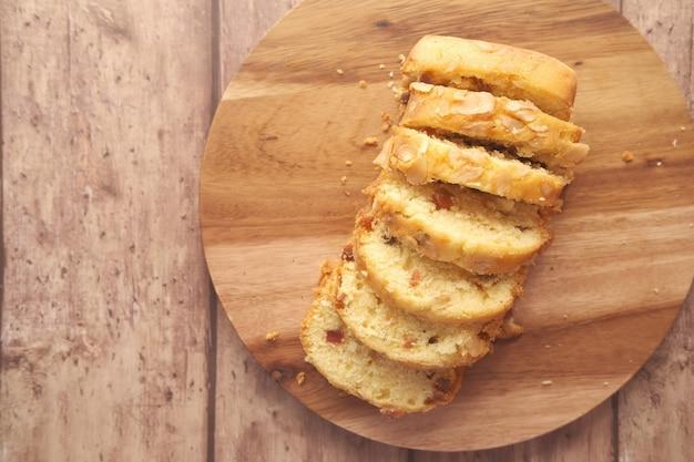 Stück obstkuchen vom bäcker auf schneidebrett