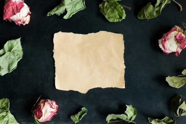 Stück papier und getrocknete rosen und blätter auf schwarzem hintergrund, draufsicht