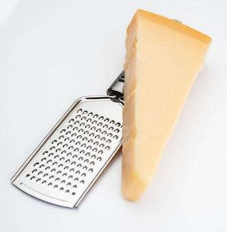 Stück parmesankäse oder grana mit reibe. isoliert