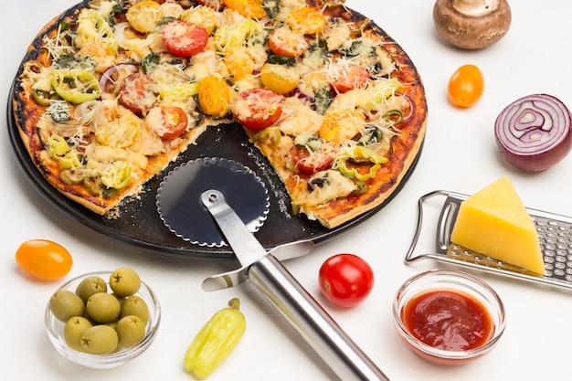 Stück pizza auf schaufel und pizza auf schwarzem teller