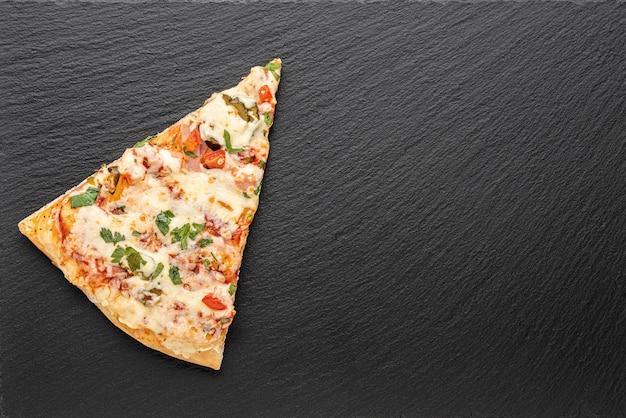 Stück pizza auf schieferbrett
