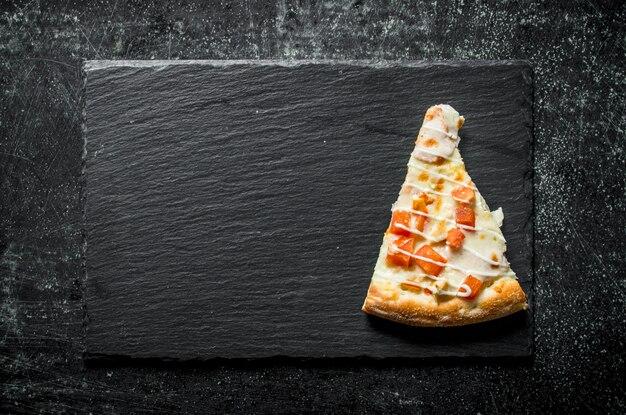 Stück pizza mit huhn, tomaten und käsesauce auf rustikalem tisch