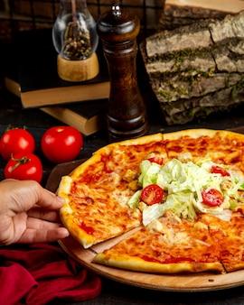 Stück pizza mit huhn und tomate auf einem holzbrett