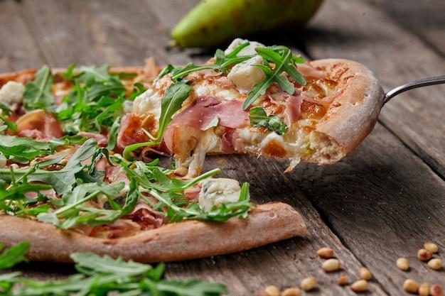 Stück pizza mit rohschinken blauschimmelkäse birne pinienkerne rucola