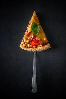 Stück pizza mit tomaten und basilikum auf einem schwarzen