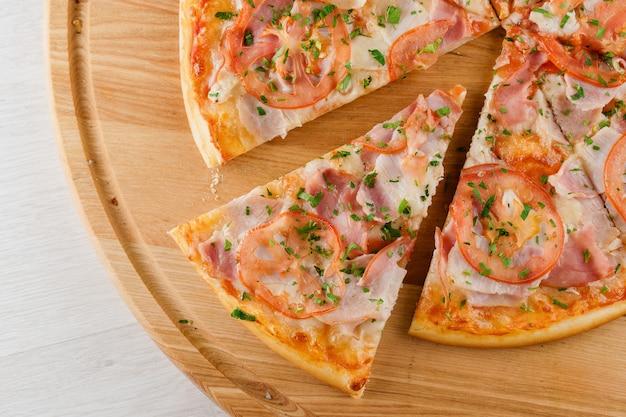 Stück pizza nahaufnahme auf dem holzschreibtisch