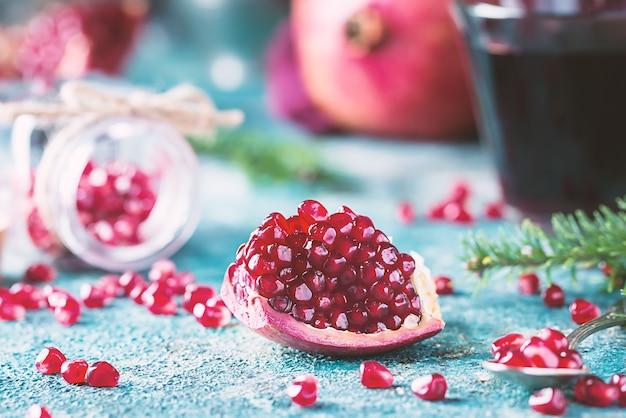 Stück reife granatapfelfrucht mit tannenzweigen auf blauem jahrgang