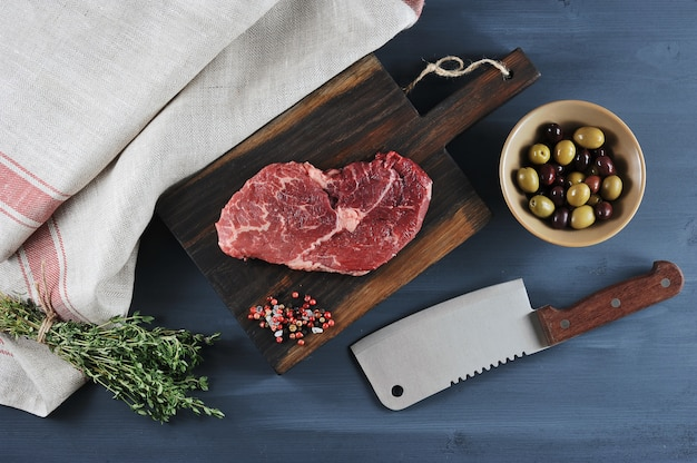 Stück rindfleisch auf einem holzbrett, ein messer für fleisch, oliven und thymian