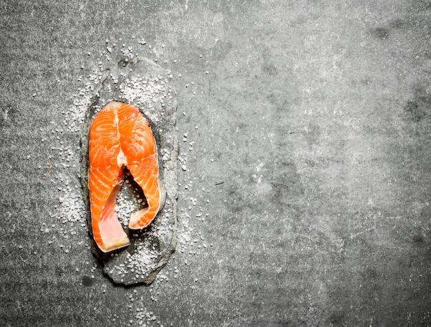 Stück rohe forelle mit salz. auf einem steinernen hintergrund.