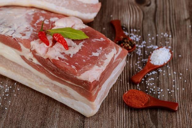 Stück rohen schweinebauch mit salz und rotem paprika auf rustikalem holztisch