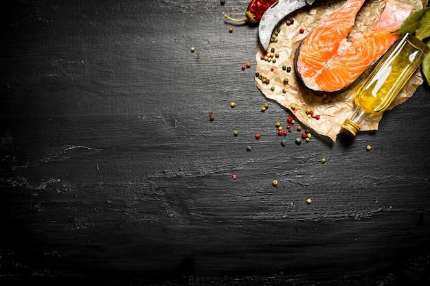 Stück roher lachs mit gewürzen und olivenöl auf schwarzer tafel.