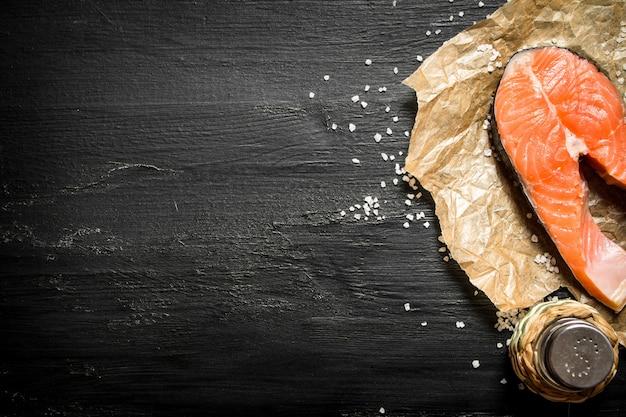 Stück roher lachs mit salz auf schwarzer tafel.