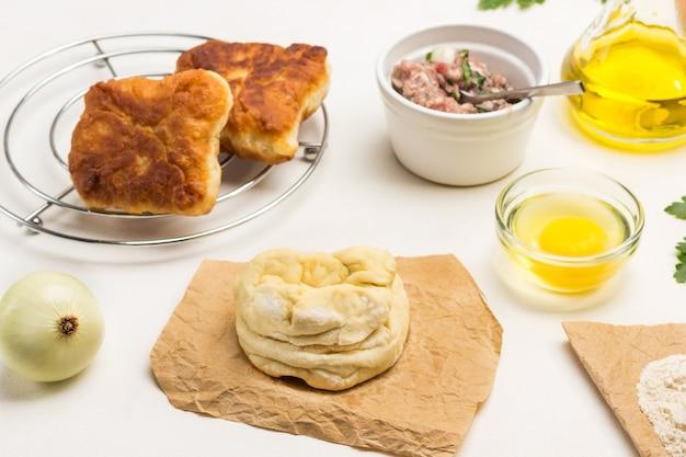 Stück roher teig auf papier. zwiebelkopf, eigelb in schüssel, hackfleisch auf dem tisch. gebratene kuchen auf heißem metallpad. weißer hintergrund. ansicht von oben
