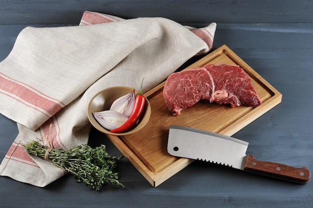 Stück rohes rindfleisch auf einem hölzernen brett