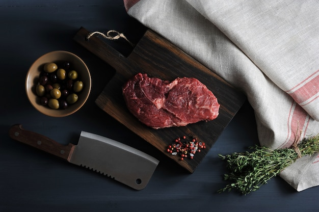 Stück rohes rindfleisch auf einem holzbrett, ein messer für fleisch, oliven und thymian