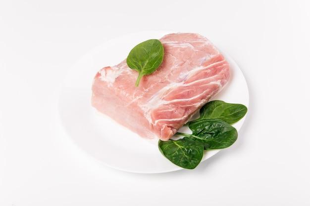 Stück rohes schweinefleisch mit spinat auf einer weißen keramikplatte. ganzes stück fleisch auf kopierplatz