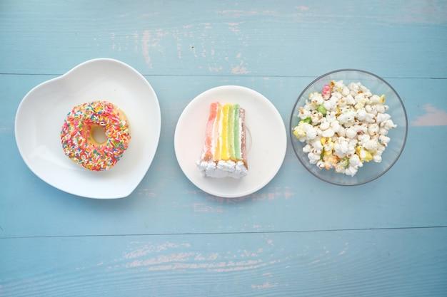 Stück sahnetorte donuts und popcorn auf dem tisch