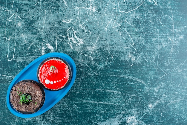 Stück schokolade und erdbeerkuchen auf blauem teller.