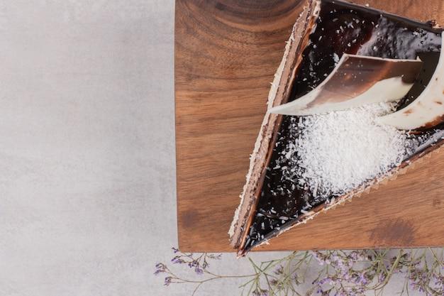 Stück schokoladenkuchen auf holzbrett.