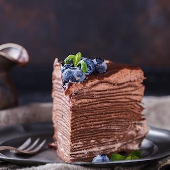 Stück schokoladenkuchen aus schokoladenpfannkuchen mit zuckerguss, mit blaubeeren