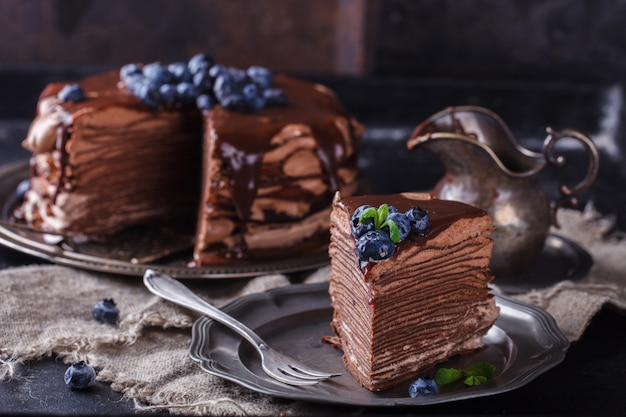 Stück schokoladenkuchen aus schokoladenpfannkuchen mit zuckerguss