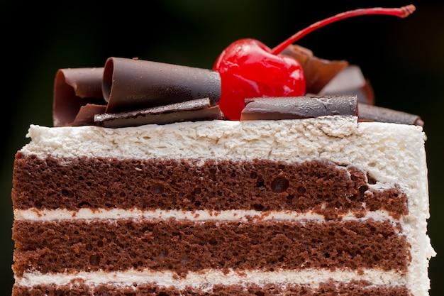 Stück schokoladenkuchen mit dem vanillebereifen und kirschgelee, überstiegen mit weißem käse