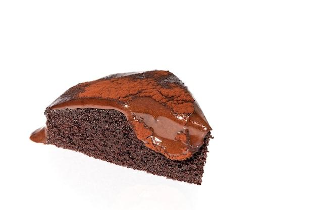 Stück schokoladenkuchen mit geschmolzener ganache auf weißem hintergrund